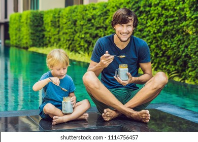 Father and son eat dessert with chia seeds and mangoes by the pool in the morning. healthy eating, vegetarian food, diet and people concept.