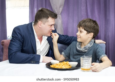 Father and son eat fried potatoes in a restaurant