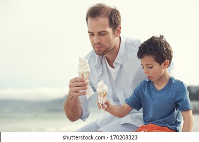 Father and son eating icecream together at the beach on vacation having fun with melting mess
