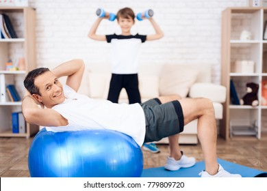 Father and son are engaged in fitness together with fitball. They do different exercises at home.