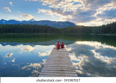 father and son enjoying a peaceful sunset over Leech lake in Jasper National Park