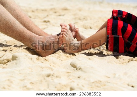 father and son feet on summer beach, family relax