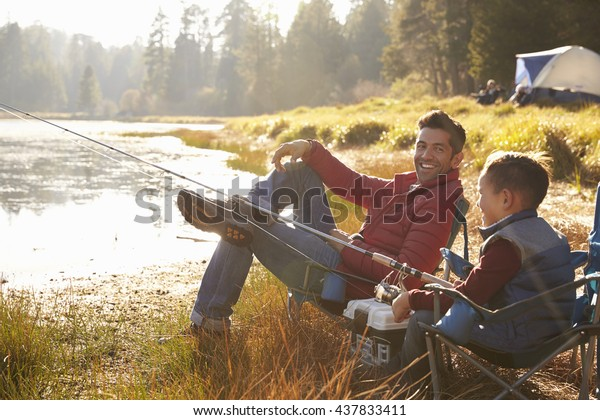 Father and son fishing by a lake, dad looks to camera