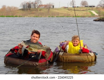 Father and son fishing - in float tubes or belly boat with a big Largemouth Bass and small drum fish