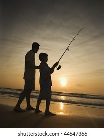 Father and son fishing in ocean surf at sunset.  Vertically framed shot.