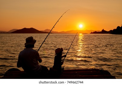 Father and son fishing on wooden wharf at sunset