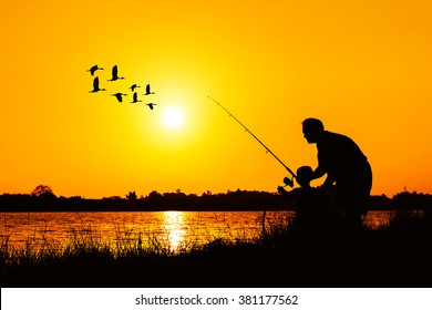 father and son fishing in the river sunset background