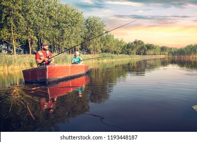father and son with fishing rods  fishing in a wooden boat against background of beautiful nature and lake or river