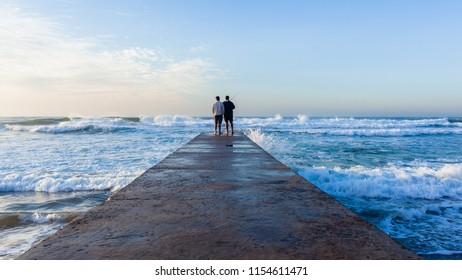 Father Son fishing silhouetted unidentified on beach jetty waters edge with ocean waves early morning blue sky landscape.