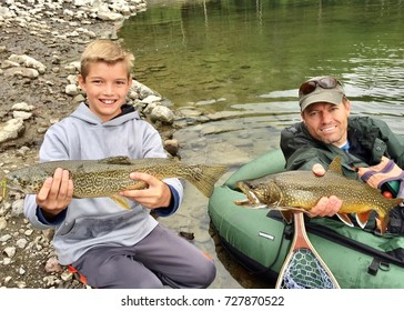 Father and son fishing together, with their catch of large fish