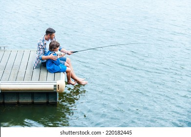 Father and son fishing. Top view of father and son fishing together on quayside