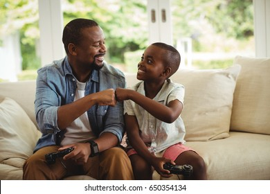 Father and son fist bumping while playing video game at home