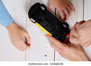 Father and son fixing toy car. Man Fixing Toy With Screwdriver Boy helping him. Family concept
