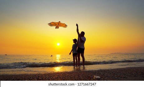 Father And Son Flying Kite on Sea Coast with nice Orange Sky Sunset. Steadicam Shot
