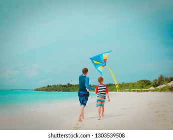 father and son flying kite on beach, family vacation