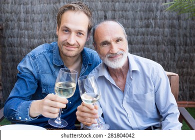 Father and son in garden drinking wine
