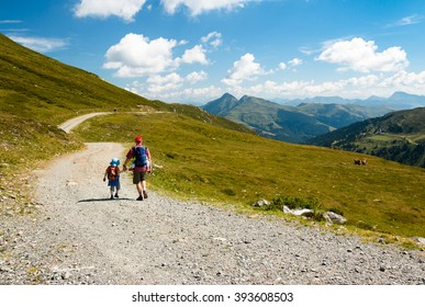 father with son and girl in baby carrier walking together on a mountain path in austrian alps