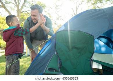 Father and son giving a high five after setting up the tent at campsite