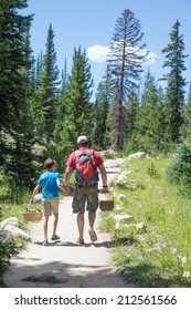 Father and son go hand in hand along the trail into the woods in search of mushrooms. Uinta Wasatch Cache National Forest, Utah