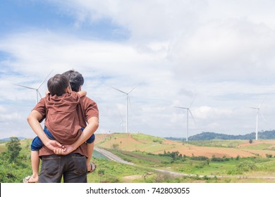Father and son go to the wind turbine field on holiday
