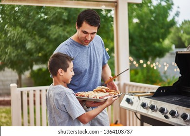 father and son grilling hot dogs together on backyard gas grill