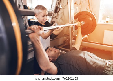 Father and son in the gym. Father and son spend time together and lead a healthy lifestyle. The father lifts the barbell and the son helps him.