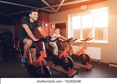 Father and son in the gym. Father and son spend time together and lead a healthy lifestyle. A man and a son are engaged in exercise bikes together.