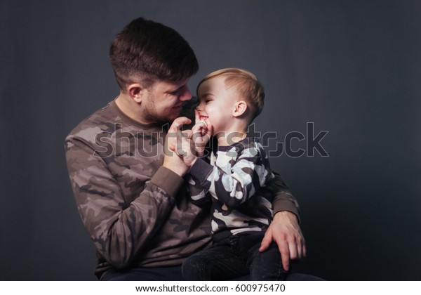 Father and son. Handsome boy with white hair playing with dad. A happy family. Friendship between father and son, Photoshoot in the studio on a gray monophonic background. Clothes military style.