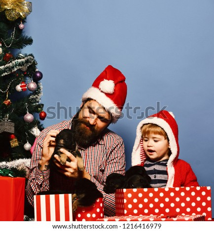 e8b0be38ee3fd Father and son with happy faces unpack present boxes on blue background.  Xmas holiday concept