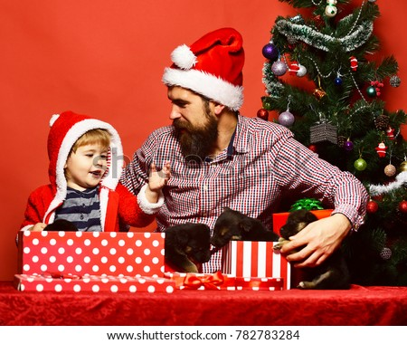 2bf83cae26bf3 Father and son with happy faces unpack presents on red background. Dad with  beard and