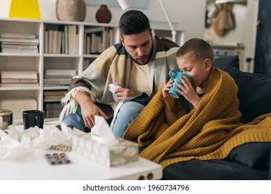 father and son have coronavirus. they sitting at home drinking tea