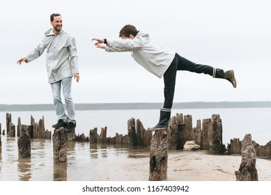 Father and son have a fun and doing joga exersises in raincoart near the sea