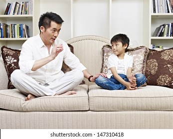 father and son having a conversation on couch at home.