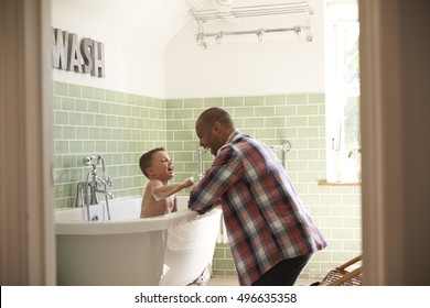 Father And Son Having Fun At Bath Time Together