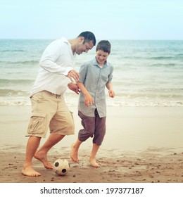 Father and son having fun on the beach and playing with a ball