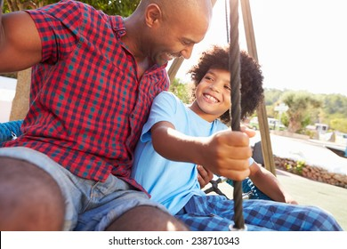 Father And Son Having Fun On Swing In Playground