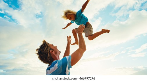 Father and son having fun on the beach at sunset, father throwing young boy up into the air