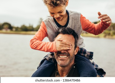 Father and son having fun spending time together playing outdoors. Boy closing the eyes of his father sitting on his shoulders.
