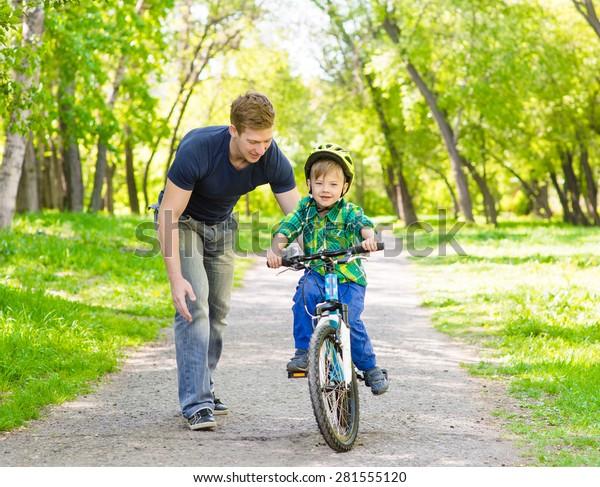 father and son having fun weekend biking