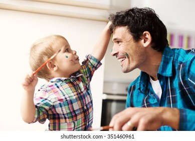 Father and son having a good time. Kid is painting father's face with watercolors. Shallow depth of field.