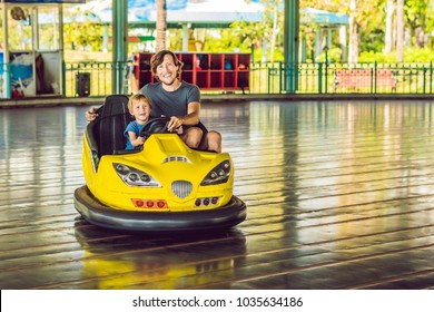 Father and son having a ride in the bumper car at the amusement park