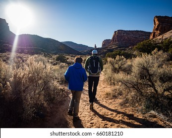 Father and son hiking in the Colorado National Monument. Monument Canyon Trail with the Independence Monument in the distance in the late afternoon on a sunny November day.