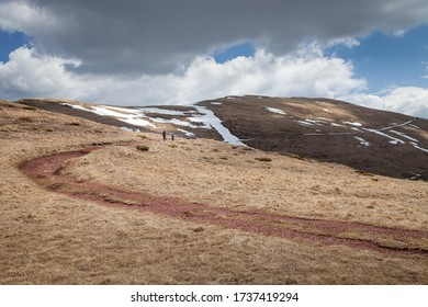 Father and son hiking down the mountain peak on the curvy mountain track covered by red rocks and remaining snow, under dramatic, cloudy sky
