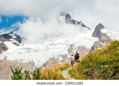Father and son hiking in French Alps in summer vacation. The Aiguille des Glaciers, mountain in the Mont Blanc massif. View From Chapieux valley, Savoie, France.