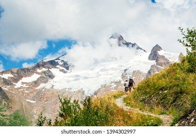 Father and son hiking in French Alps in summer. The Aiguille des Glaciers, mountain in the Mont Blanc massif. View From Chapieux valley, Savoie, France. Family vacation background. Fatherhood concept.