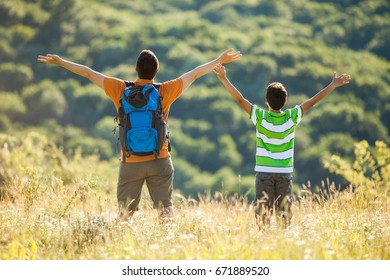 Father and son are hiking in nature in summer. They are enjoying fresh air.