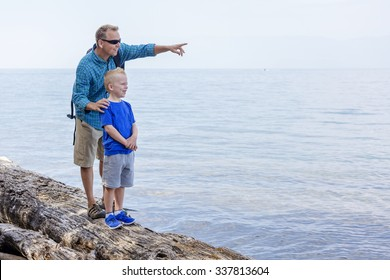 Father and son hiking together along a scenic lake. Lots of copy space and full length photo