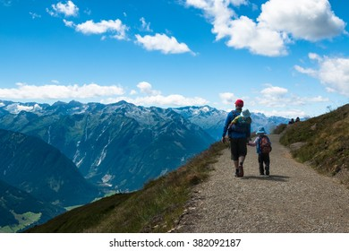 father with son hiking together in high mountains in austrian alps on wildkogel in salzburg