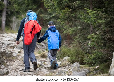 father and son hiking together in the mountains with backpack in fall mountain track