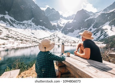 Father and son hiking traveler rest and drink tea near the mountain lake
